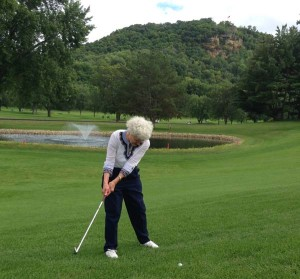 Susan Miller takes a stroke for her daughter on the approach to the 18th green, with Granddad's Bluff in the background.