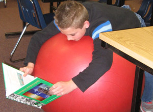 Longfellow 6th-grader Markos Cash demonstrates how he likes to read using a classroom stability ball purchased with grant funding from LPEF.