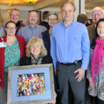 Annette O'Hern with a photo from Pine Ridge, with a number of friends and supporters, including (back row, from left): Liz Arnold and Dr. Sig Gundersen III from Gundersen Medical Foundation; Central Principal Troy McDonald; Lisa Sauer from Gundersen; retired administrator Jerry Berns; (middle row from left) Carolynn Devine from Gundersen, Brian O'Hern and Marcia Morales from Gundersen.