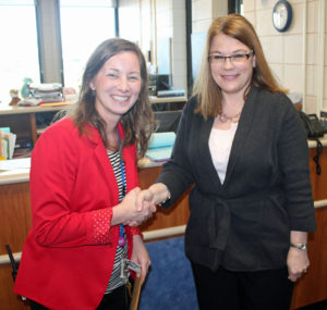 Hintgen Principal Amy Oliver, left, receives a grant from Past Board President Tammy Larson in support of Responsive Classroom training for Hintgen teachers.